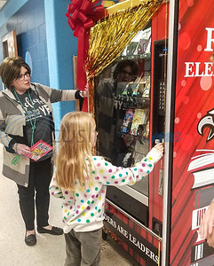 Rusk Elementary second grader Dalaney Jinkins, 7, puts the first token into the school's new book vending machine during the grand reveal on Thursday, January 30. Students will be rewarded with a token to pick a book from the machine for good behavior, acts of kindness and other positive actions. (Jessica T. Payne/Tyler Morning Telegraph)