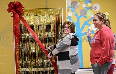 Rusk Elementary library assistant Angela Corley cuts the ribbon at the unveiling of the school's new book vending machine on Thursday, January 30. The machine was installed as part of a special student incentive program. (Jessica T. Payne/Tyler Morning Telegraph)