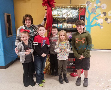 Rusk Elementary School students (from left) Alli Dowling, Dylan Starkey, Clayton Oliver, Dalaney Jinkins and Talon Sunday stand with library assistant Angela Corley in front of the school's new book vending machine.  The machine stood covered in the hallway since early January for students to guess what was underneath. (Jessica T. Payne/Tyler Morning Telegraph)