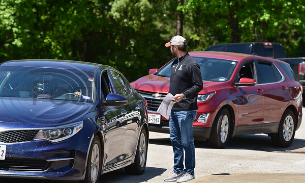 Cars lined the entry way of Rusk High School on Tuesday, April 14 as students were instructed to remain in their vehicles while picking up their cap and gowns.