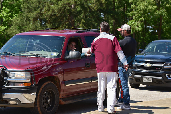 Rusk High School staff hand out senior cap and gowns while adhering to social distancing regulations during cap and gown pick up day on Tuesday, April 14. Students were told to pick up their graduation attire in a drive-thru manner and remain in their cars due to the Coronavirus pandemic.