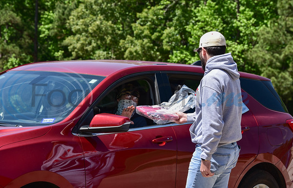 Rusk High School teacher Tony Shinalt hands out senior cap and gowns on Tuesday, April 14. Students were instructed to remain in their cars in accordance with the six feet distance recommendation due to the Coronavirus pandemic.