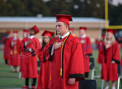 Rusk High School senior Nick Acker, who will go on to play football for Howard Payne University, crosses his heart during the National Anthem at the school's graduation ceremony on Friday, June 5.