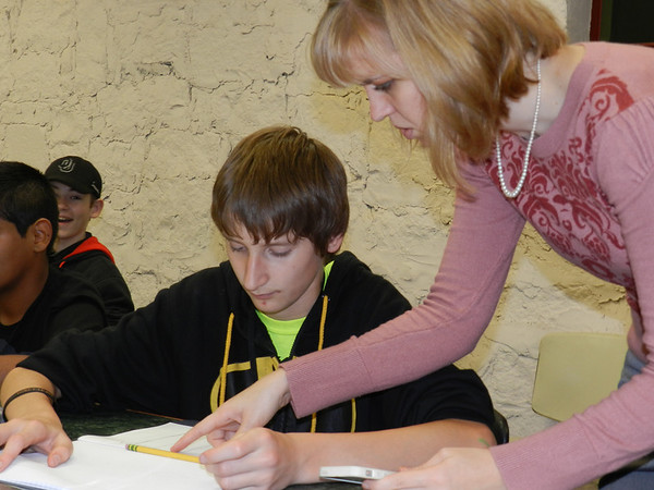 Math teacher Megan Rowan helps Alice Robertson Junior High School student Colton Merriman with a division problem during an after-school tutoring session at Muskogee Teen Center. Students are spending six weeks improving math and reading skills.