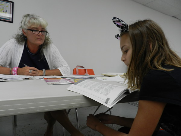 Reading teacher Tina Green helps Alice Robertson Junior High student Hailey Tucker improve reading comprehension. Tucker said she reads better because of AR's after-school tutoring program at Muskogee Teen Center.