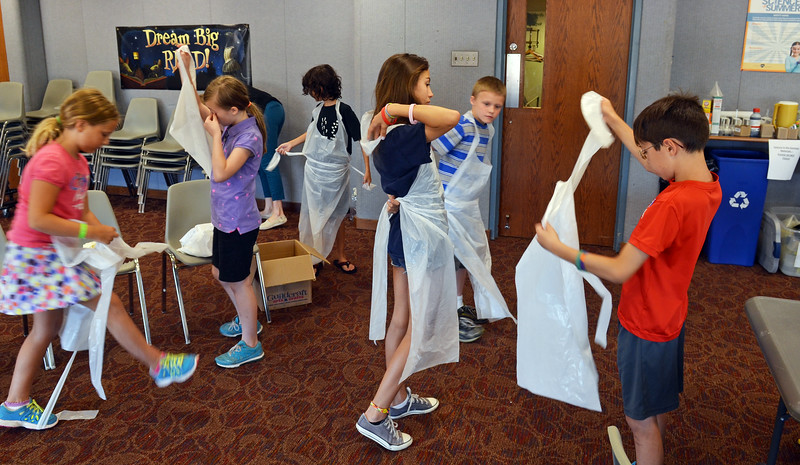 Children put on aprons as they get ready for Science in the Summer activity at the Indian Valley Library.   Thursday,  July 17, 2014.   Photo by Geoff Patton