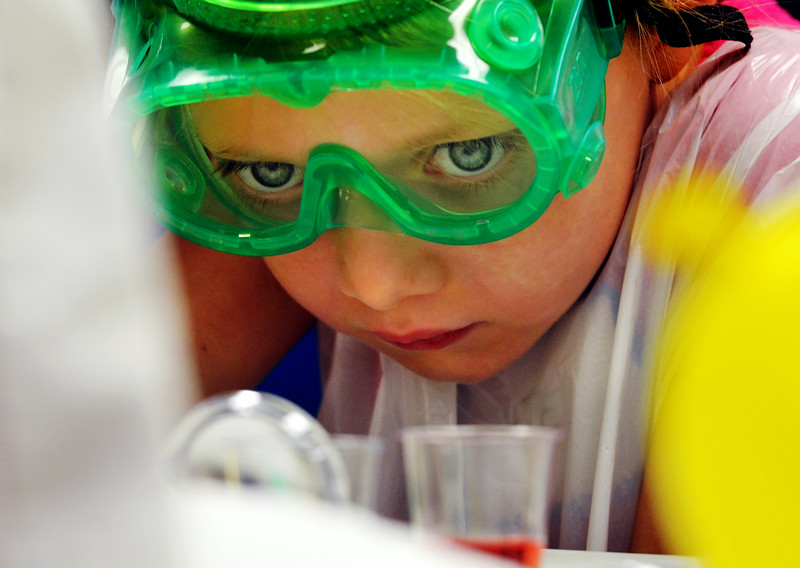 A young girl looks closely at a container of water containing food coloring during the Science in the Summer program at the Upper Dublin Library.   Tuesday,  July 1, 2014.   Photo by Geoff Patton