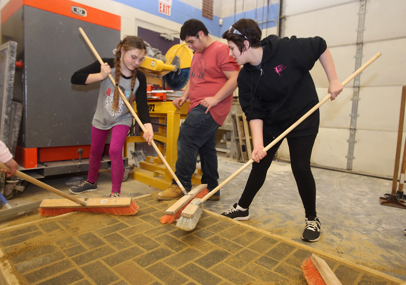 Seventh graders from Billerica and Bedford learn about different shops at Shawsheen Tech's Project Explore, after their regular school day. From left, Hera Lewis, 12, of Billerica, Joseph Arkalis, 13, of Burlington, and Nicole Hatch, 12, of Burlington, sweep sand into the gaps between patio bricks in Masonry. (SUN/Julia Malakie)
