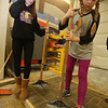 Seventh graders from Billerica and Bedford learn about different shops at Shawsheen Tech's Project Explore, after their regular school day. Jacqueline Genetti, 13, left, and Hera Lewis, 12, both of Billerica, tamp down bricks after filling gaps with sand in Masonry. (SUN/Julia Malakie)