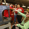 Project Explore at Shawsheen Tech, where 7th graders try out different shops. From left, Alyssa MacKenzie, Geena Medeiros, Jacara DeGree, and Morghan Kushmerek, all 13 and from Billerica, learn how to use an arbor press to make circular metal pieces concave, one step in making a candle holder, in Metal Fabrication. (SUN/Julia Malakie)