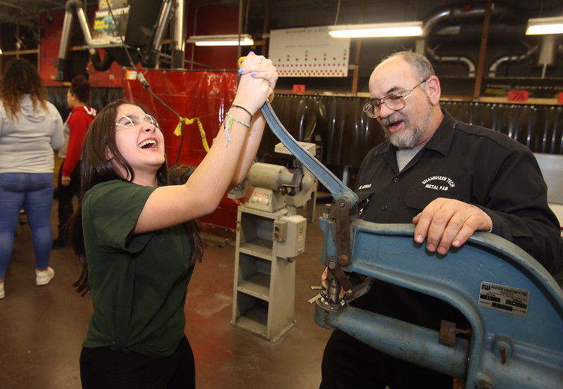 Project Explore at Shawsheen Tech, where 7th graders try out different shops. Maria Rose, 12, of Billerica, uses a punch press to bend petals of a stamped metal part for a candle holder, as Metal Fabrication instructor Tom Lothian of Northwood, N.H., looks on. (SUN/Julia Malakie)