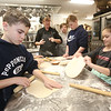 Project Explore at Shawsheen Tech, where 7th graders try out different shops. From left, Patrick Hall, 13, of Billerica, Culinary chief instructor Meg Costello of Amesbury, Brady Baldwin, 13, of Burlington, Tyler Normant, 13, of Billerica, and Camdyn Folta, 12, of Billerica, learning how to make pizza. (SUN/Julia Malakie)