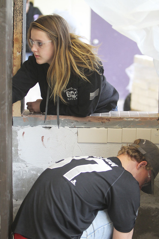 . Shawsheen Tech masonry students are building a Dunkin\' Donuts for the school\'s annual open house. Emma Barnes, 16, of Billerica, and James Mackenzie, 17, of Tewksbury, both juniors, work on the takeout window booth. (SUN/Julia Malakie)