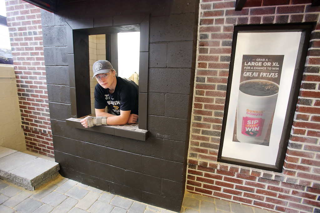 . Shawsheen Tech masonry students are building a Dunkin\' Donuts for the school\'s annual open house. James Mackenzie, 17, of Tewksbury, a junior, in the takeout window. (SUN/Julia Malakie)