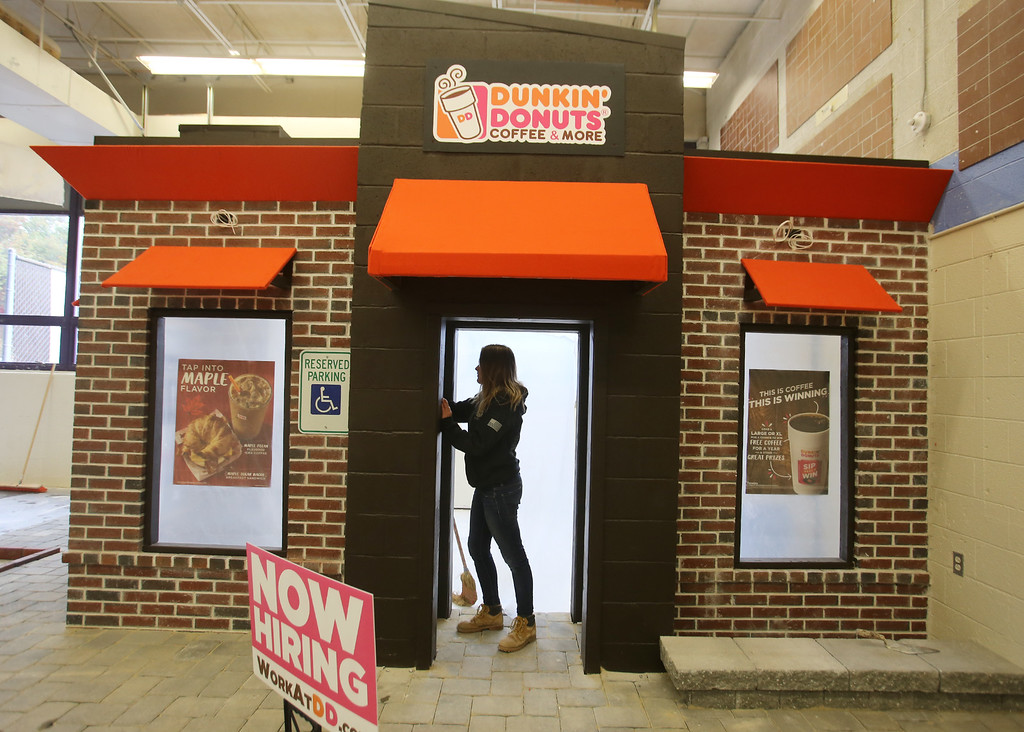 . Shawsheen Tech masonry students are building a Dunkin\' Donuts for the school\'s annual open house. Junior Emma Barnes, 16, of Billerica, buffs the tiles inside the entry. (SUN/Julia Malakie)