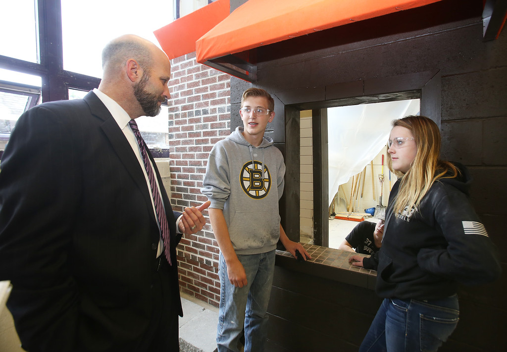 . Shawsheen Tech masonry students are building a Dunkin\' Donuts for the school\'s annual open house. Superintendent-director Tim Broadrick talks to juniors Derek Leffler, 16, of Tewksbury, and Emma Barnes, 16, of Billerica, about math being their favorite academic subject. (SUN/Julia Malakie)
