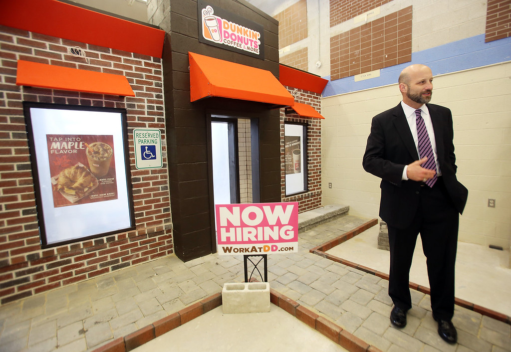 . Shawsheen Tech masonry students are building a Dunkin\' Donuts for the school\'s annual open house. Superintendent-director Tim Broadrick talks to reporter. (SUN/Julia Malakie)