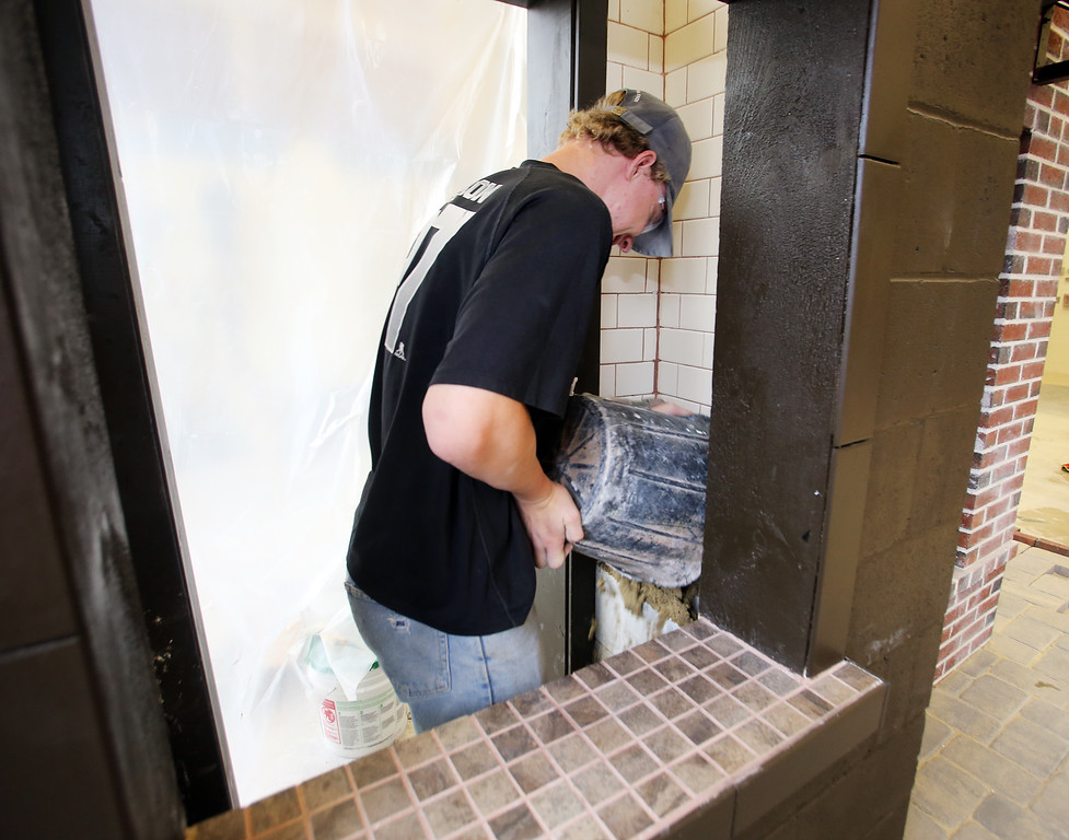 . Shawsheen Tech masonry students are building a Dunkin\' Donuts for the school\'s annual open house. James Mackenzie, 17, of Tewksbury, a junior, fills in a cinderblock to lay tile in the takeout window. (SUN/Julia Malakie)