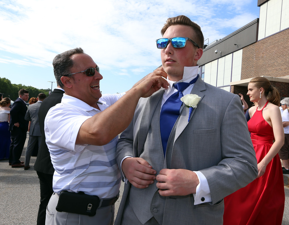 """. Pre-prom procession at Shawsheen Tech. Paul Troisi of Billerica helps his daughter\'s boyfriend Mark Companeschi of Wilmington with his collar. Troisi said \""""he\'s taking very good care of my daughter so I need to make sure he looks good.\"""" (SUN/Julia Malakie)"""