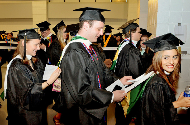 L-R Kaitlyn Buscone of Medfield Ma, Andrew Federico of Plainview NY and Catherine Dondero of Norwood Ma help each other out with gowns. Siena College commencement at the Times Union Center in Albany, Sunday  May 18,  2014 (Mike McMahon - The Record)