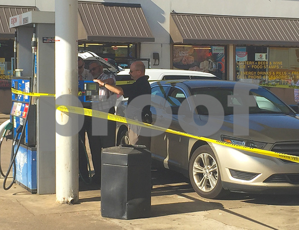 Investigators with the Northeast Texas Financial Crimes Task Force working on removing a credit card skimmer device they located Thursday at the Exxon gas station at 2615 E. Commerce St. (LouAnna Campbell/Tyler Morning Telegraph)