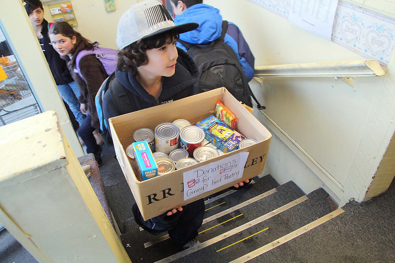 Sky View Middle School students dropped off food to Ginny's Food Pantry on Thursday afternoon after school. Carrying in some of the food they collected is sixth grader Nico Meidy, 11. SENTINEL & ENTERPRISE/ JOHN LOVE