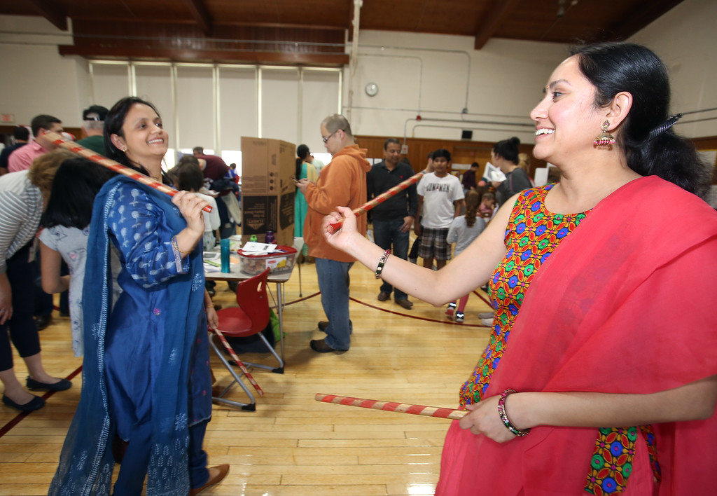 . South Row School International Festival in Chelmsford. Anu Gudbole, left, and Sowmya Angadi, both of Chelmsford and South Row parents, dance the dhandiya, a Northern Indian form of dance with sticks to make noise. (SUN/Julia Malakie)