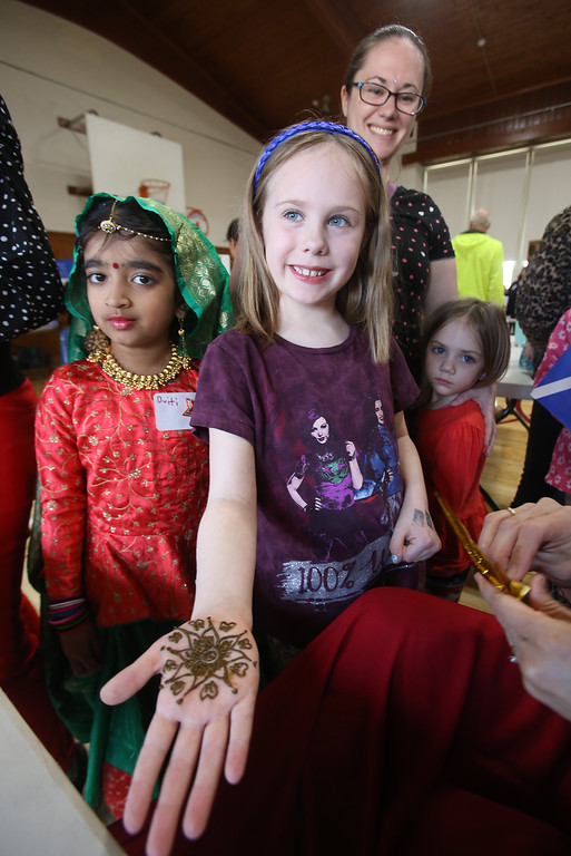 . South Row School International Festival in Chelmsford. Lillian Abbott, 7, of Chelmford, showing her henna painted hand, with her mother Tammy Abbott and sister Evelyn, 4, rear, and 1st grader Dviti Patel, 7, left. (SUN/Julia Malakie)