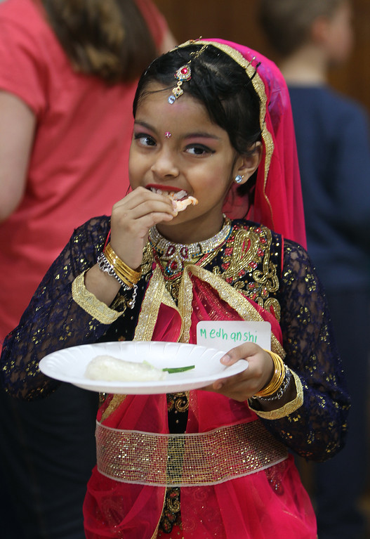 . South Row School International Festival in Chelmsford. Medhanshi Bhowmick, 7, a 1st grader at South Row, eats a spring roll. She\'s wearing a lahenga, and was going to be doing a bolu, an Indian dance. (SUN/Julia Malakie)