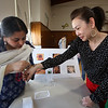 South Row School International Festival in Chelmsford. Shruti Srivastava of Chelmsford paints henna on the hand of Melody Suong, one of the chairpersons of the festival. (SUN/Julia Malakie)