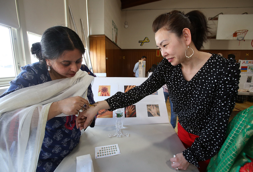 . South Row School International Festival in Chelmsford. Shruti Srivastava of Chelmsford paints henna on the hand of Melody Suong, one of the chairpersons of the festival. (SUN/Julia Malakie)