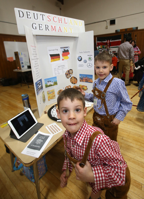 . South Row School International Festival in Chelmsford. Harrington Elementary School kindergarten student Hayden Hunnewell, 6, front, with his brother, South Row 2nd grader Hunter Hunnewell, 8, who was passing out pretzel samples at the Germany booth. (SUN/Julia Malakie)