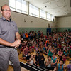 South Street Elementary Principal Jon Thompson takes a long look at Otis the pig before planting the pig with a kiss during the last school assembly of the year on Wednesday morning. Thompson has previously promised his school that he would kiss a pig if they read over one million pages of book during the school year. SENTINEL & ENTERPRISE / Ashley Green