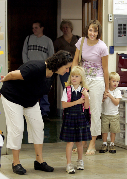 E.L. Hubbard Photography<br /> Teacher's aide Angela Leonhardt greets Kylie Spade as Kylie's mother Katie Spade, and brother, Michael, 3, drop her off for her first day of kindergarten at St. Joseph.