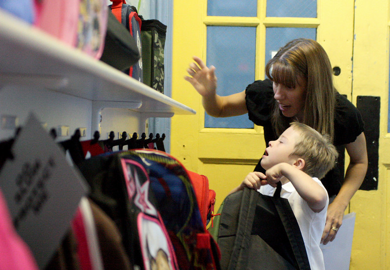 E.L. Hubbard Photography<br /> Kindergarten teacher Tessa Crooke shows Michael Meehan the hook where he will hang his book bag on the first day of school at St. Joseph.