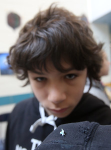 Students at the Stoklosa Middle School made over 1,000 paper cranes in an art project, with each student making at least one, to promote peace and other wishes. Christian Montalvo, 8th grader, with his tiny folded paper crane on his sleeve. It's normally kept in a glass jar so it doesn't get lost. (SUN/Julia Malakie)