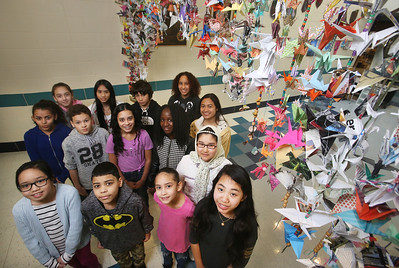 Some of the students at the Stoklosa Middle School who made over 1,000 paper cranes in an art project, with each student making at least one, to promote peace and other wishes. From left, front: 5th graders Thu Vu, Luis Gomez, Knalee Ortega and Jennifer Thok. Middle row: 8th grader Ariana Santiago, 7th graders Israel Rentas, Yuliana Lugo and Celia Flomo, and 6th grader Fatema Ahmad Ali. Back row: 8th grader Nina Morales, 7th grader Julie Sok, and 8th graders Christian Montalvono, Bianca Jimenez and Daryan Kong. (SUN/Julia Malakie)