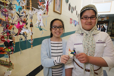 Students at the Stoklosa Middle School made over 1,000 paper cranes in an art project, with each student making at least one, to promote peace and other wishes. Amonge them are 5th grader Thu Vu, left, and 6th grader Fatema Ahmad Ali.  (SUN/Julia Malakie)