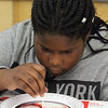 """Stoklosa Middle School Summer Program. Eliane Amani, 11, does """"Kitchen Chemistry"""", using milk, food coloring and Dawn detergent as a catalyst to make swirling designs. (SUN/Julia Malakie)"""