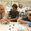 """Stoklosa Middle School Summer Program. From left, teacher Nancy Kanellas of Lowell, Braylon Ly, 12, and Chris Lozada, 11, all of Lowell, use """"Kitchen Chemistry"""", using milk, food coloring and Dawn detergent as a catalyst to make swirling designs. (SUN/Julia Malakie)"""