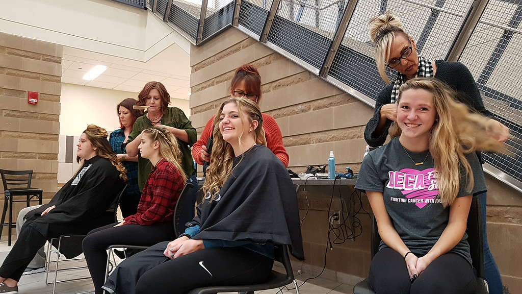 . Tewksbury High DECA members get their hair done by volunteers ahead of this evening\'s annual TMHS DECA fashion show, to benefitr the Meghan McCarthy Research Fund, for pediatric brain tumor research.  Kelly Golini, 18, center, has hair done by Sheryl Liggiero of Tewksbury, owner of Fresh Looks Salon in Tewksbury. Sammi LaLonde, 17, right, has hair done by Julie Erbetta of Tewksbury, whose son Christian is in the show. (SUN/Julia Malakie)