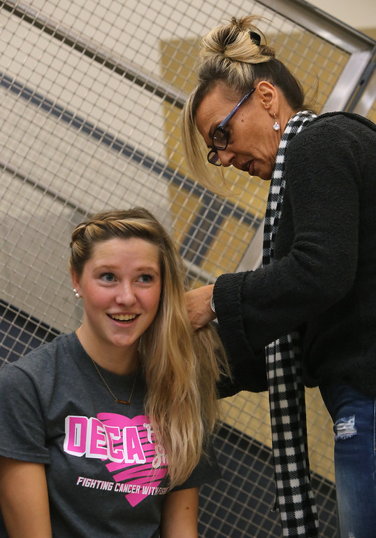 . Tewksbury High DECA members get their hair done by volunteers ahead of this evening\'s annual TMHS DECA fashion show, to benefitr the Meghan McCarthy Research Fund, for pediatric brain tumor research. Sammi LaLonde, 17, has hair done by Julie Erbetta of Tewksbury, whose son Christian is in the show. (SUN/Julia Malakie)
