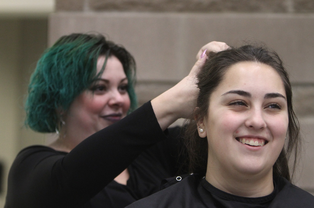 . Tewksbury High DECA members get their hair done by volunteers ahead of this evening\'s annual TMHS DECA fashion show, to benefitr the Meghan McCarthy Research Fund, for pediatric brain tumor research. Carrie O\'Connor of Billerica, who works at Fresh Looks Salon in Tewksbury, does hair for Jacqui Marchant, 17, of Tewksbury, a senior. (SUN/Julia Malakie)