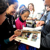 "Minacangjue, left, Feng Xingjuan, and Baiyang, a sixth-grader from Tibet, look at  Tibet photos taken by Lisa Wertz, back center, a Casey Middle School teacher.<br /> A delegation from Tibet, organized by the Boulder-Lhasa Sister City Project, visited Casey Middle School on Tuesday. For more photos and a video of the delegation, go to  <a href=""http://www.dailycamera.com"">http://www.dailycamera.com</a>.<br /> Cliff Grassmick/ February 22, 2011"