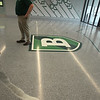 Superintendent Tim Piwowar gives a tour of the new Billerica Memorial High School. Brushed metal in the floor is the Concord River, on a map of Billerica that makes up the main lobby floor. (SUN/Julia Malakie)