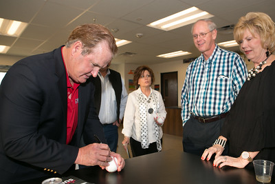 Baseball Hall of Fame catcher Jim Sundberg autographs a baseball for Jordan and Carla Wilton of Weatherford.