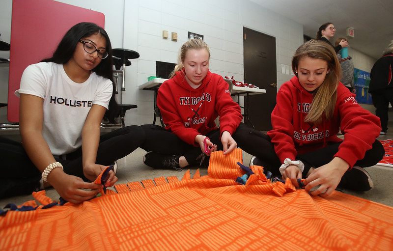 Tyngsboro Middle School students tie together two layers of fleece to make blankets for the homeless. From left, eighth graders Meshwa Patel, 13, Kristi DeBruin, 14, and Ava Anderson, 14, all of Tyngsboro. (SUN/Julia Malakie)
