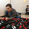 Tyngsboro Middle School students tie together two layers of fleece to make blankets for the homeless. Seventh graders Dominick Tinnirella, 13, left, and Ryan Kaminski, 12, both of Tyngsboro. (SUN/Julia Malakie)