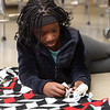 Tyngsboro Middle School students tie together two layers of fleece to make blankets for the homeless. Sixth grader Dahlya Zoua, 12, of Tyngsboro, ties layers together. (SUN/Julia Malakie)