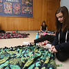 Tyngsboro Middle School students tie together two layers of fleece to make blankets for the homeless.  Eighth graders Xenia Politis, 14, of Lowell, right, and Sophia Silva, 14, left rear, and Sophia Panagakis, 14, both of Tyngsboro. (SUN/Julia Malakie)